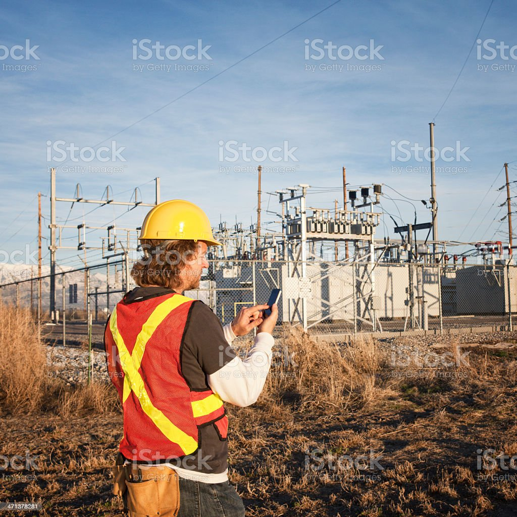 Power Line Technician Using Smart Phone royalty-free stock photo