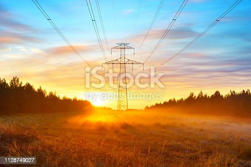 Power lines and scenic sunrise landscape with morning fog at meadow by the forest, Spain