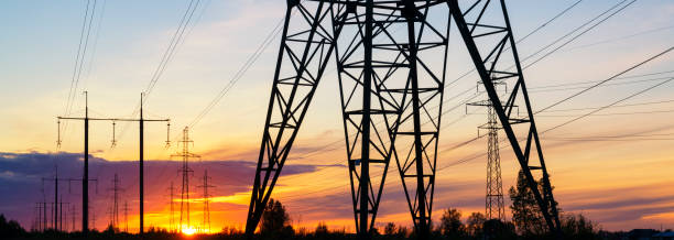 Power lines at the sunset header. Electricity distrubution and environment concept