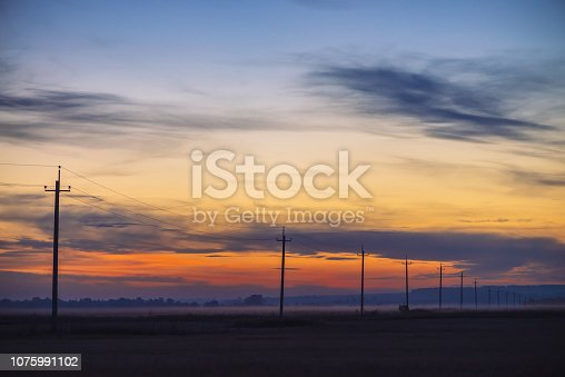 Power lines in field on sunrise background. Silhouettes of poles with wires at dawn. Cables of high voltage on warm orange blue sky. Power industry at sunset. Multicolored picturesque vivid sky.