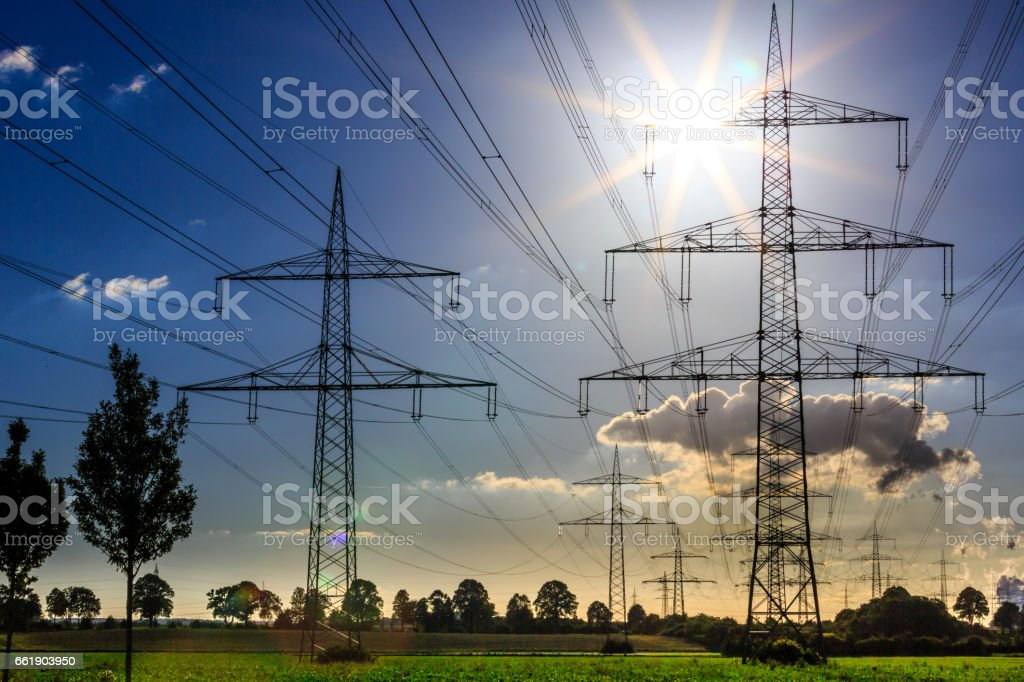 power lines on a green field in the sunset stock photo