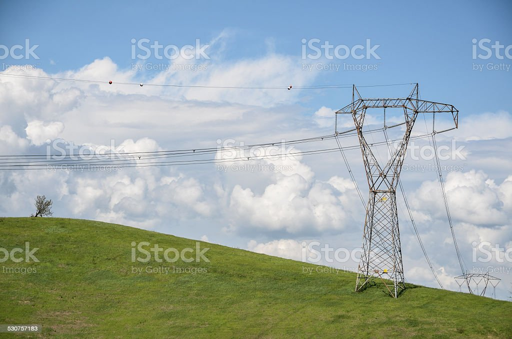 power lines on a green hill under cloudy blue sky stock photo