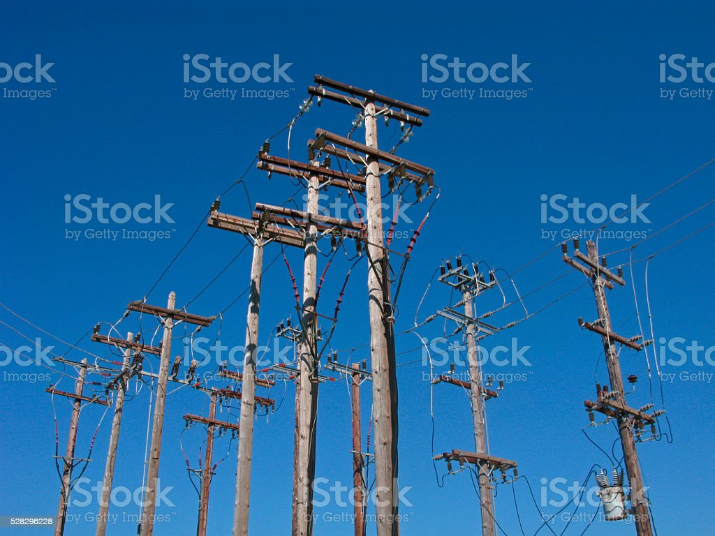 Power lines on wooden poles stock photo