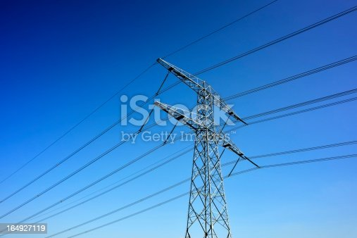 Large electricity pylon and energy cables with a blue sky.