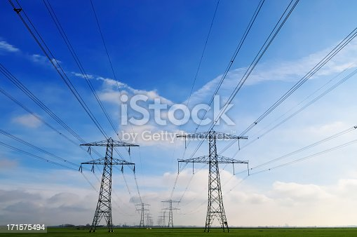 Silhouettes of power lines in a flat landscape and blue sky.