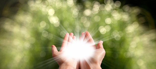 Conceptual vitality image of close up glowing lights in palm of hands over shiny defocused green landscape