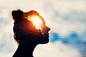 The Light Head. Silhouette of young woman on sky background with sun in her head.
