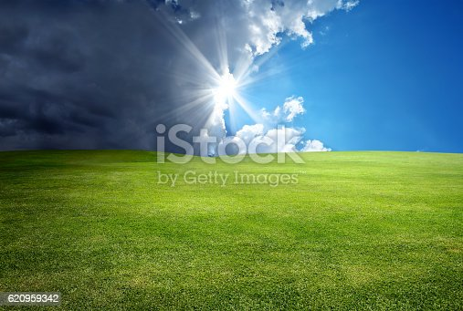 green landscape over cloudy and sunny sky with sunbeam.