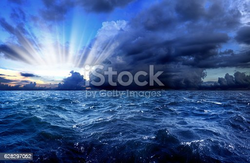 seascape with waves in stormy day over cloudy sky and sunbeam