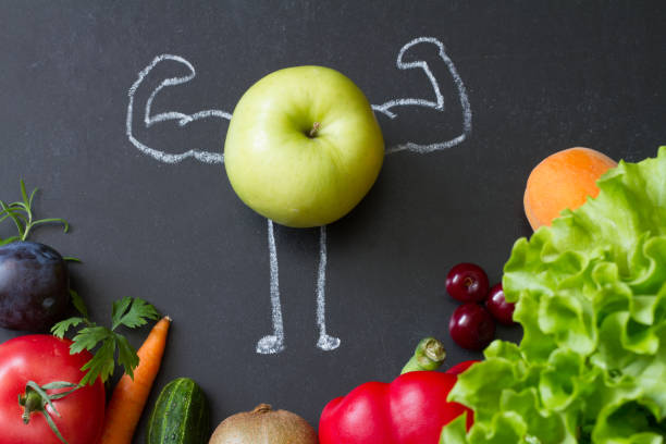 Power of vitamins diet abstract concept with green muscles apple on blackboard stock photo
