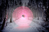 Red Circular light in the middle of a small path in a snow covered forest