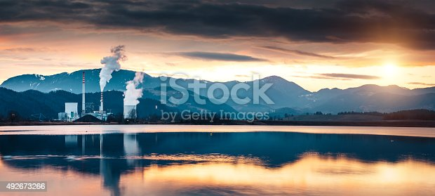 Coal-fired power plant destroying the environment with releases. Panoramic image at sunset with reflection in the lake.