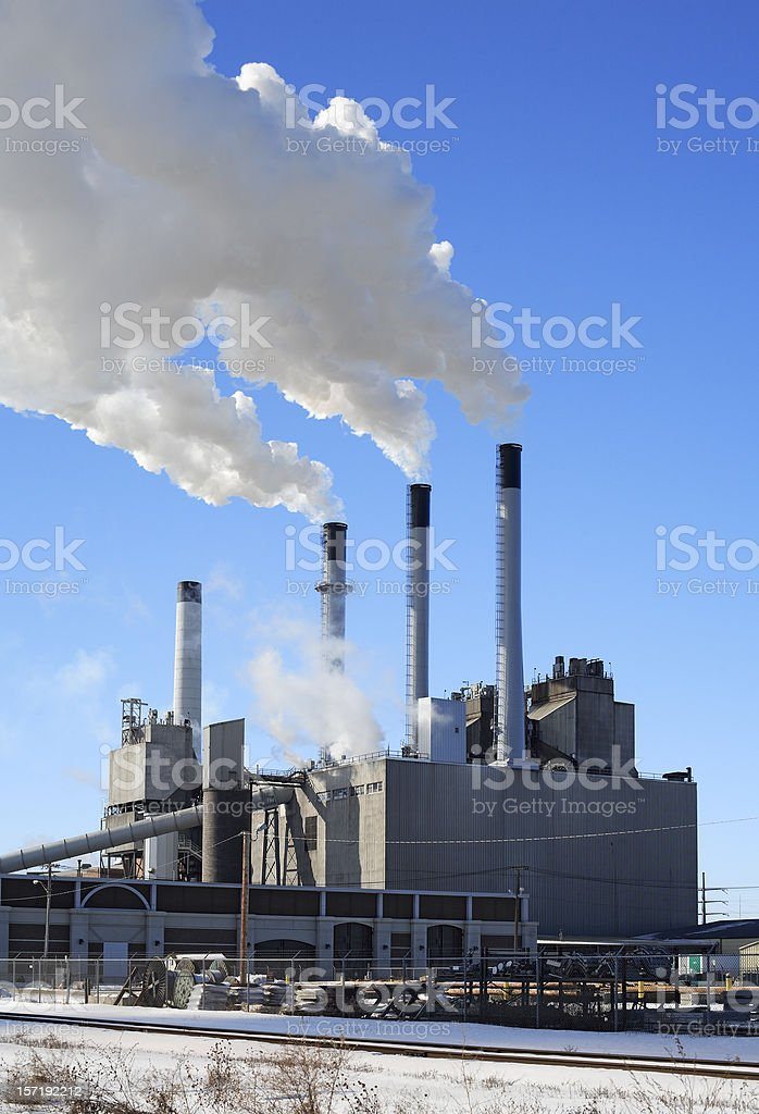A power plant in the winter time pumping out smoke royalty-free stock photo