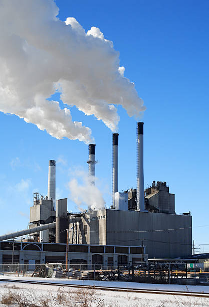 A power plant in the winter time pumping out smoke stock photo