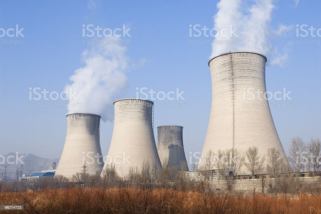 A power plant with four smoke stacks in deserted location royalty-free stock photo