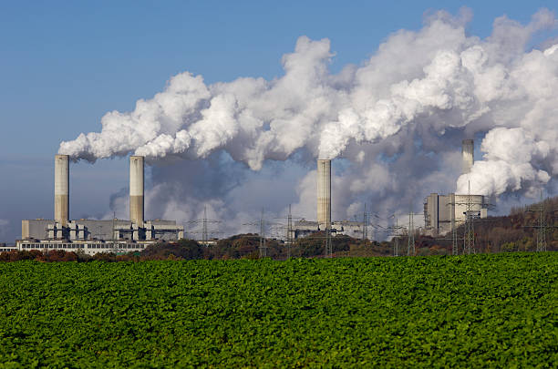 Power plant with pollution Coal burning power plant with pollution. carbon dioxide stock pictures, royalty-free photos & images