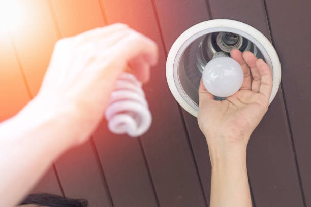 Power saving concept. Asia man changing compact-fluorescent (CFL) bulbs with new LED light bulb. Power saving concept. Asia man changing compact-fluorescent (CFL) bulbs with new LED light bulb. canadian football league stock pictures, royalty-free photos & images
