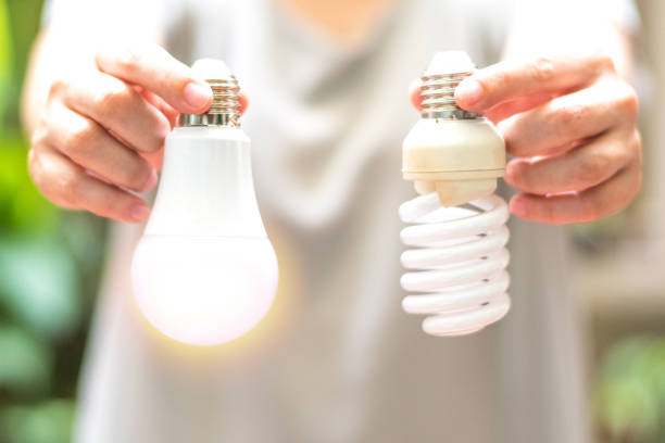 Power saving concept. Hands holding new Light Emitting Diode ( LED ) light bulb with light on and blur spiral compact-fluorescent (CFL) bulbs behind for copyspace. Power saving concept. Hands holding new Light Emitting Diode ( LED ) light bulb with light on and blur spiral compact-fluorescent (CFL) bulbs behind for copyspace. canadian football league stock pictures, royalty-free photos & images