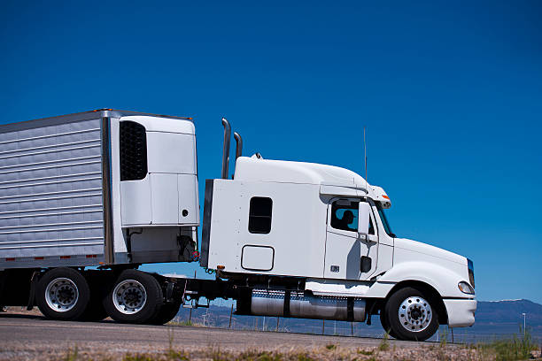Power Semi truck rig and reefer trailer side view stock photo