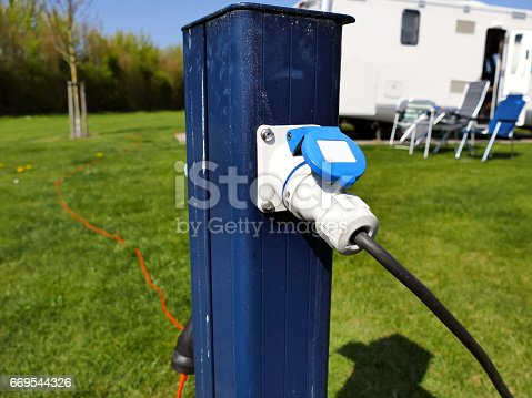 AC power sockets at a camping site, Full service campground electricity with camper motor home in background