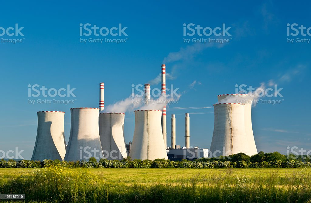 Power station in field under blue sky stock photo