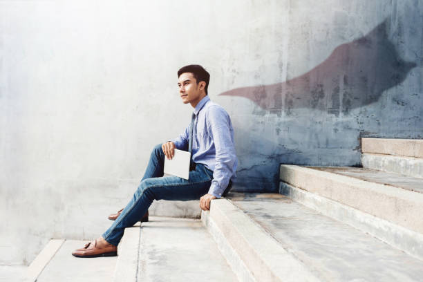 Power, Success and Leadership in Business concept, Young man sitting on office Outdoor Stair and looking forward with superhero blanket shadow shade on the wall, Side view stock photo