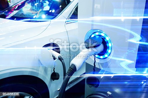 istock Power supply connect to electric vehicle for charge to the battery. Charging technology industry transport which are the futuristic of the Automobile. EV fuel Plug in hybrid car. 954558336