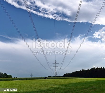 Power supply line pylon in the countryside, blue sky with clouds