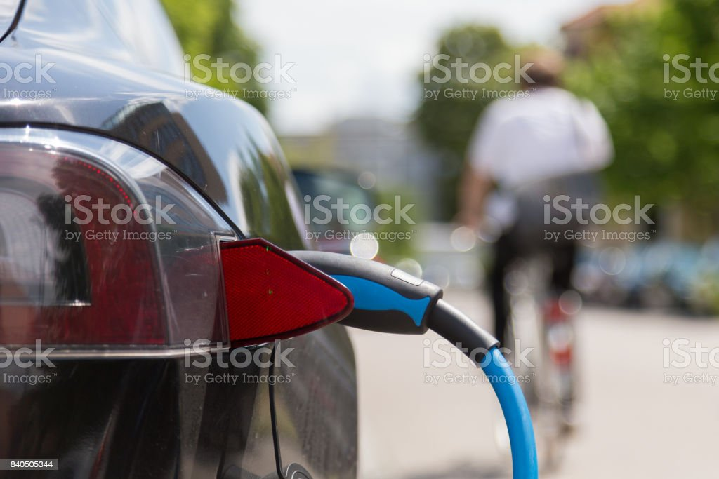 Power supply plugged into an electric car being charged. stock photo