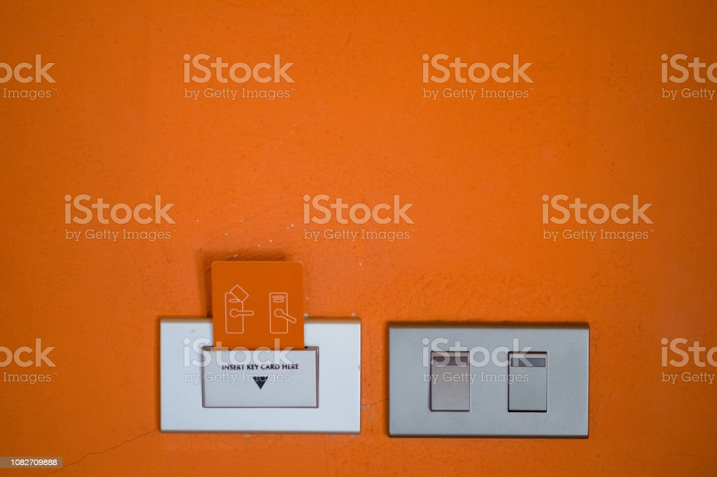Power switch and key card on orange cement wall. Warm tone orange cement stock photo