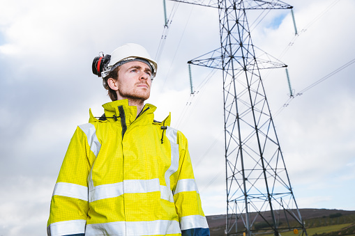 Young male power systems engineer wearing high visibility clothing and hardhat beside a high voltage power line.