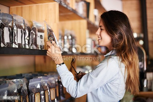 Shot of a beautiful smiling woman in a store choosing a packet of coffee beans