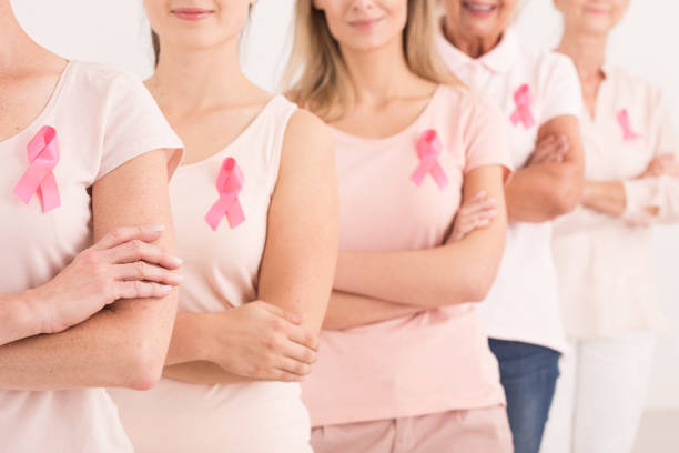 Power to fight breast cancer The power to fight breast cancer, women wearing pink ribbons for breast cancer campaign on white background film and television screening stock pictures, royalty-free photos & images