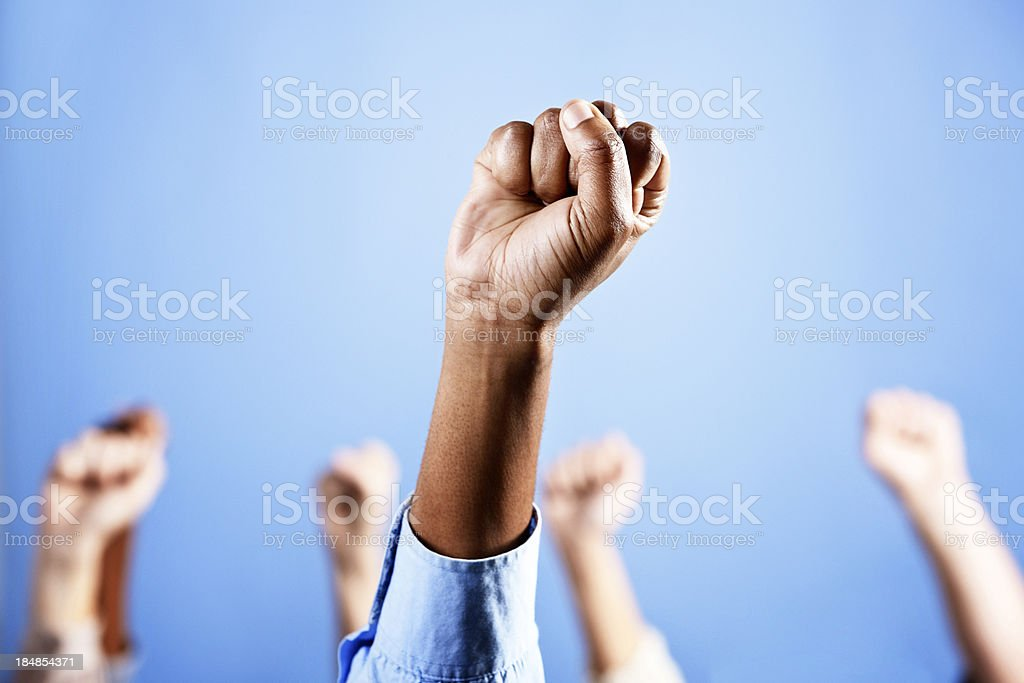 Power to the people! Clenched fist spotlit against blue royalty-free stock photo