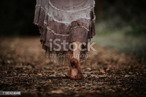 Woman wearing dirty white dress walking away barefoot on trail