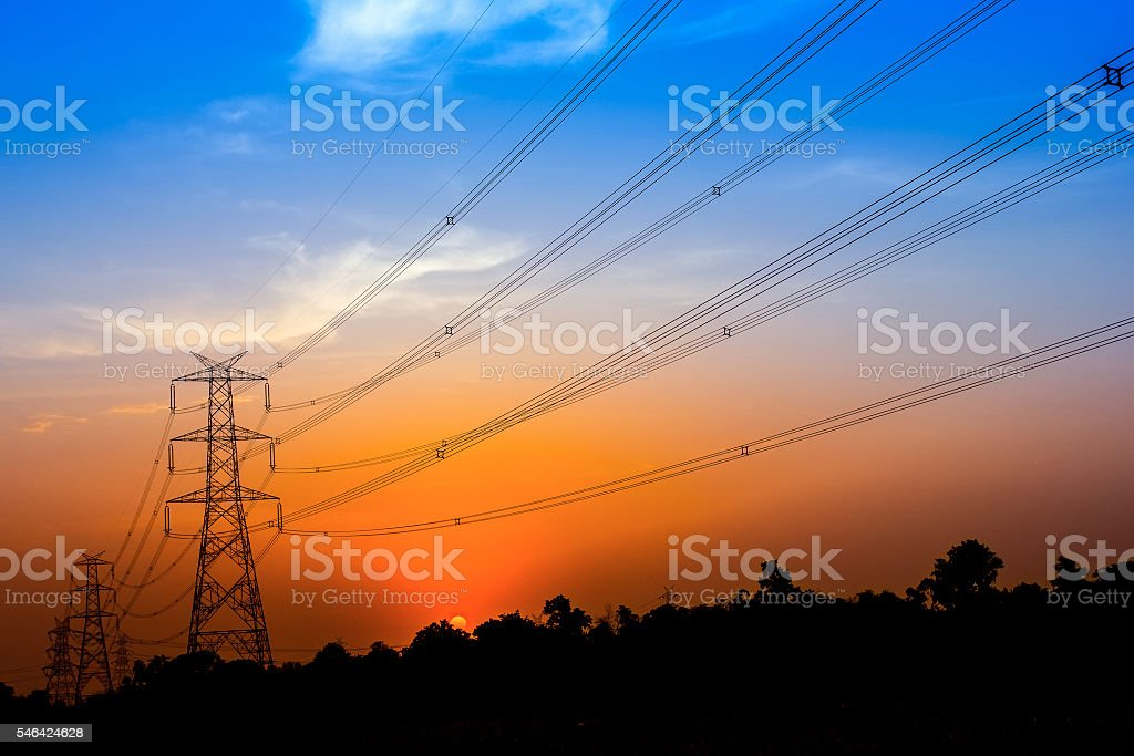 power transmission tower silhouetted against the sunset glow stock photo