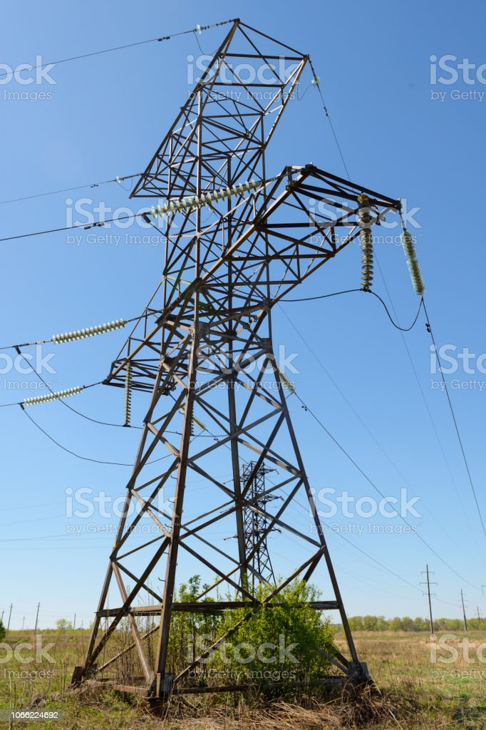 power transmission tower with electricity transmission lines in the midst of a spring green field stock photo