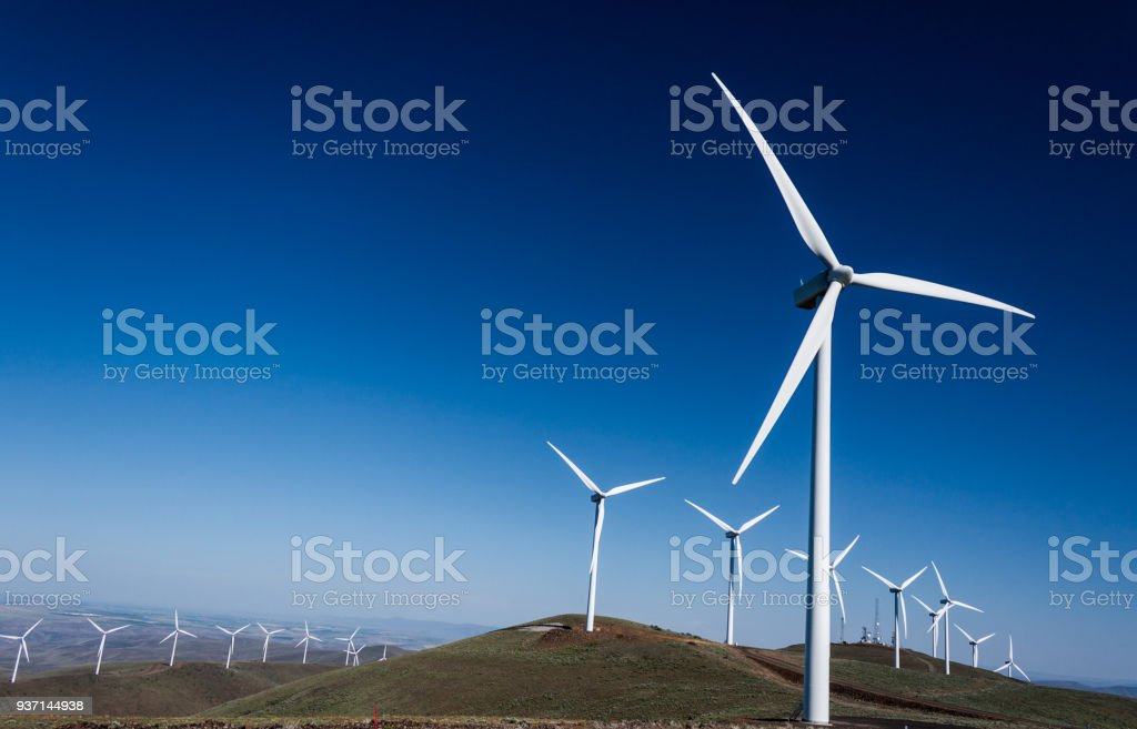 Power turbine wind mills on rolling hills with a blue sky stock photo