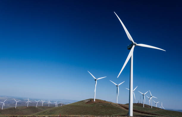 power turbine wind mills on rolling hills with a blue sky - mulino a vento foto e immagini stock