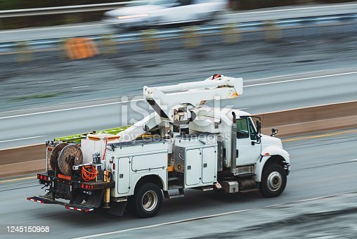Panning with a power utility truck in evening light yielding motion blur.