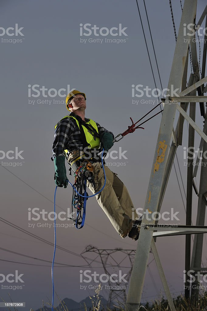 Power utility worker abseiling from pylons stock photo