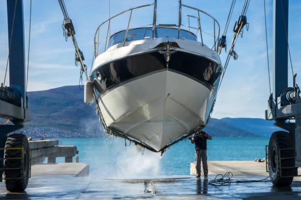 Power washing barnacles on a yacht in dry dock Montenegro, Tivat, October 30 2017. Man is working at the Navar Boatyard. He is using a pressure washer to clean the bottom of the boat while it is in dry dock. He is removing barnacles from the prop and shaft. Boats need routine cleaning and maintenance. hull stock pictures, royalty-free photos & images