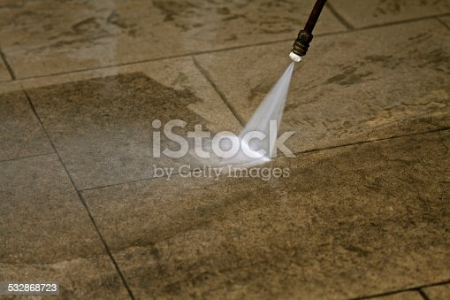 Power washing a concrete deck showing clean vs dirty