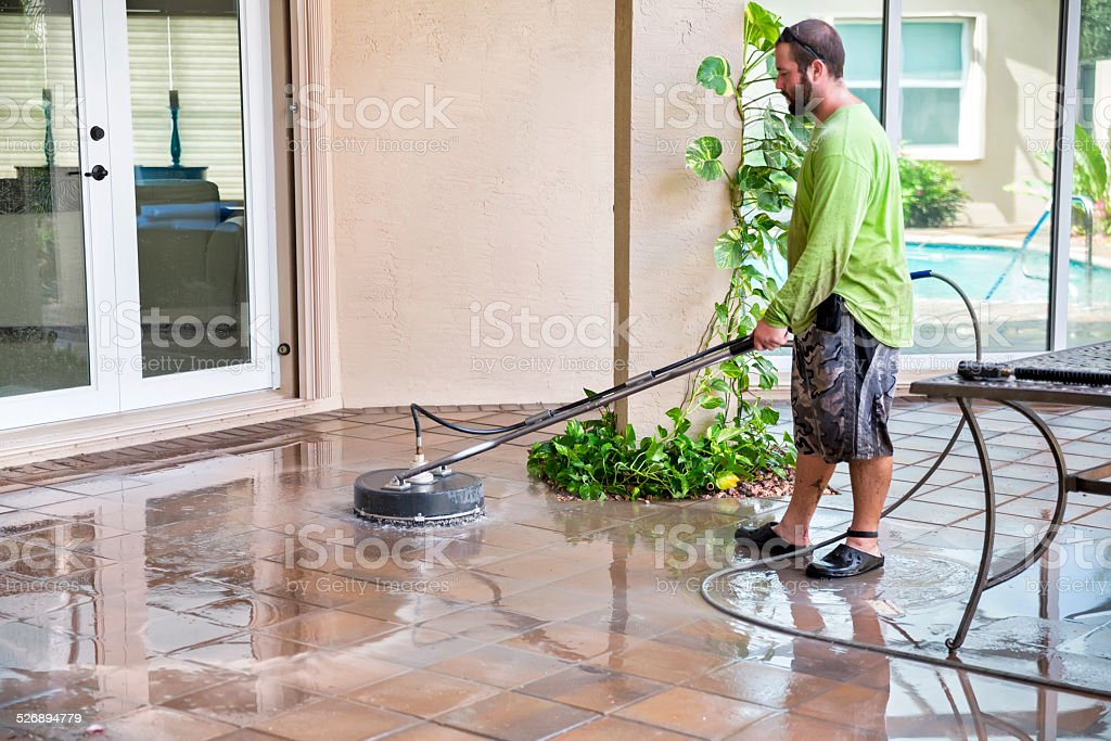 Residential Pool Cleaning : Power washing worker cleaning residential pool patio tiles