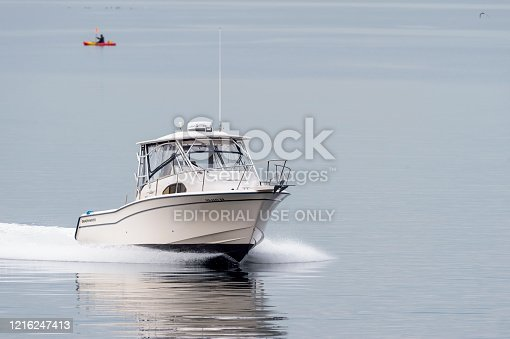 Fairhaven, Massachusetts, USA - May 1, 2019: Powerboat cruising across flat water in foggy New Bedford outer harbor