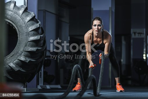 Concept: power, strength, healthy lifestyle, sport. Powerful attractive muscular woman Fitness trainer do battle workout with ropes at the gym