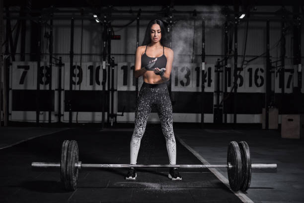 Powerful, attractive muscular girl engaged in gym, training with barbell in the gym. The athlete smeared her hands with talcum powder. stock photo