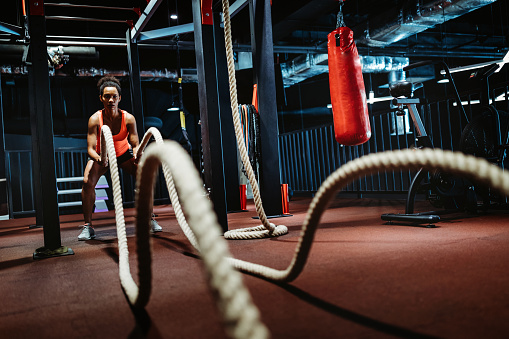 Powerful fit beautiful woman battle rope workout at the gym. Strength, healthy lifestyle, sport concept.