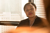 Powerful black businesswoman leader looking and listening to her colleague in office meeting