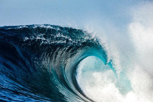 Powerful blue breaking wave breaking in the open ocean on a sunny day